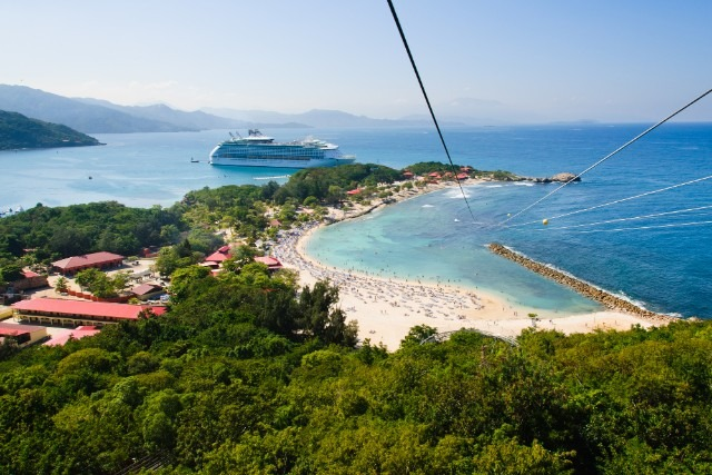 View of the ship, beaches and trees from the top of the zip line