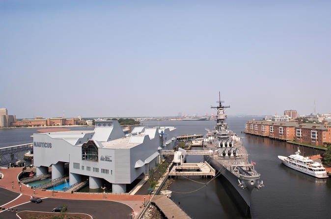 Exterior view of Nauticus and the USS Wisconsin sitting in the harbor in Norfolk, VA