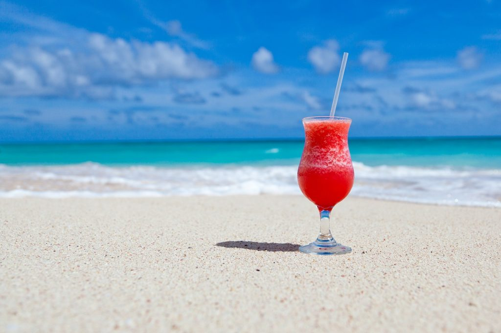 Cold fruity cocktail sitting on a white sand beach with the blue ocean in the background