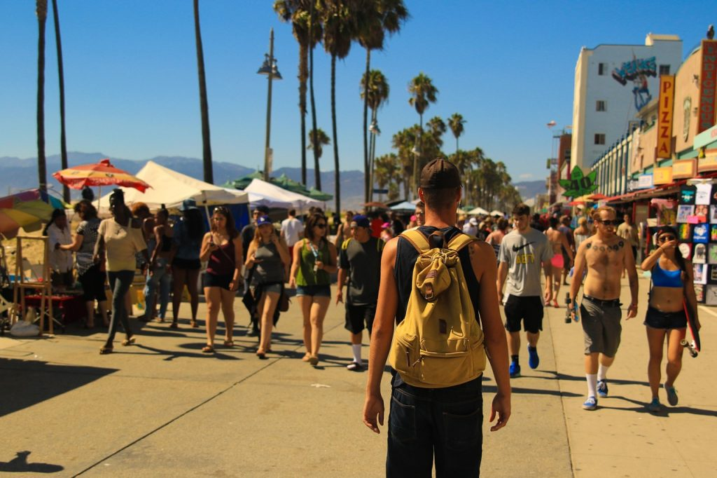 Single man walking along a beachside boardwalk walking into a crowd of people