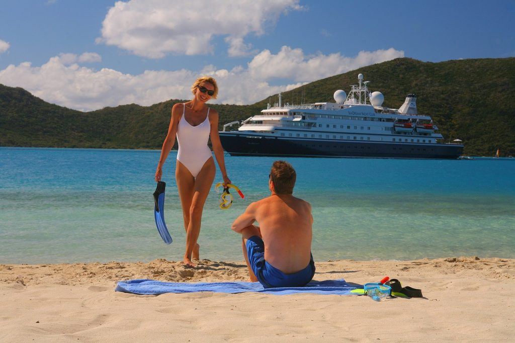 Man and woman having fun on the beach with their cruise ship in the background